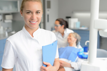 Dental assistant smiling dentist with patient