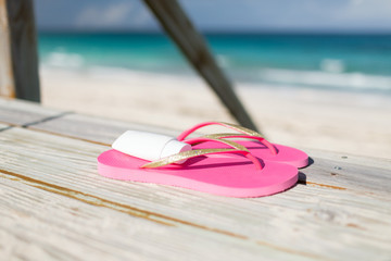 close up of sunscreen and slippers at seaside