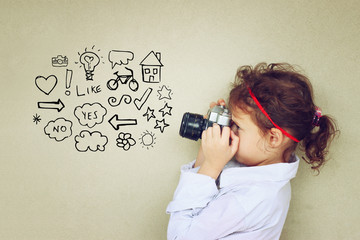 Concept of cute kid looking through vintage camera viewfinder an