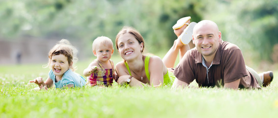 Happy family of four in summer park