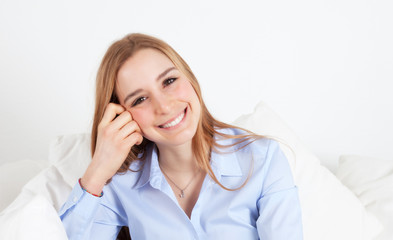 Young woman on a sofa laughing at camera