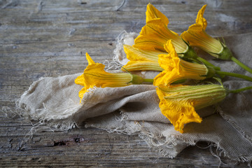 zucchini blossoms lying on rustic wooden table with jute napkin