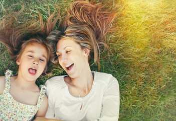 cute little girl and her mother having fun on the grass in sunny