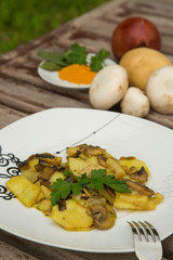Baked potatoes with mushrooms and parsley on the white plate.
