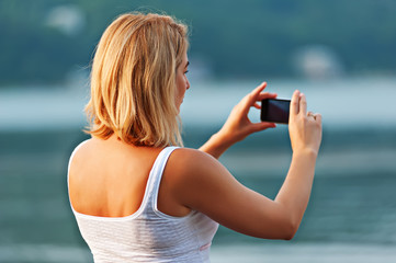 Portrait of pretty woman taking photos with mobile phone.
