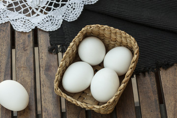 Eggs on wooden table and basket