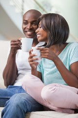 Happy couple sitting on their couch having coffee