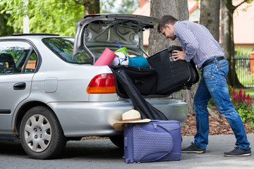 Man trying to putting a travel bags into a car