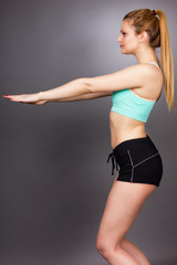 Young fitness woman doing squat exercises