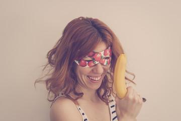 Superhero hipster girl wearing mask with banana gun