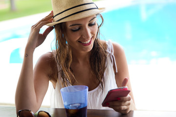 Beautiful girl taking a mobile phone at the swimming pool.