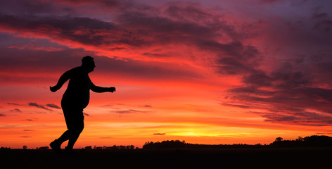 Silhouette of funny overweight man jogging at the sunset