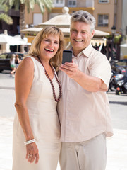 Married mature couple of travelers posing for a selfie photo