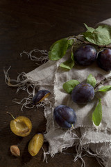 whole and slice prunes with leafs on rustic background