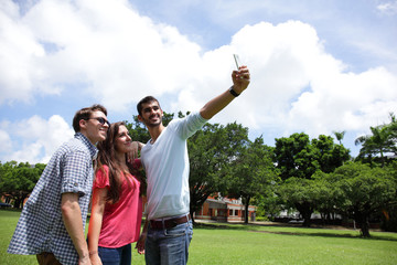 Group of happy friends taking selfie