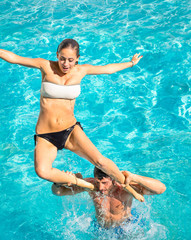 Happy young couple - Fun in swimming pool jumping and diving