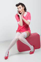 PinUp sexy girl with pink suitcase.