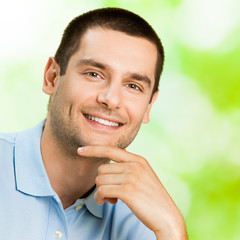 Portrait of young attractive smiling man, outdoor