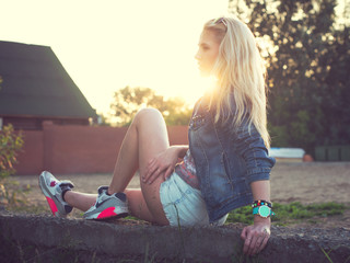 Sunny portrait of a beautiful fashion young girl summer evening