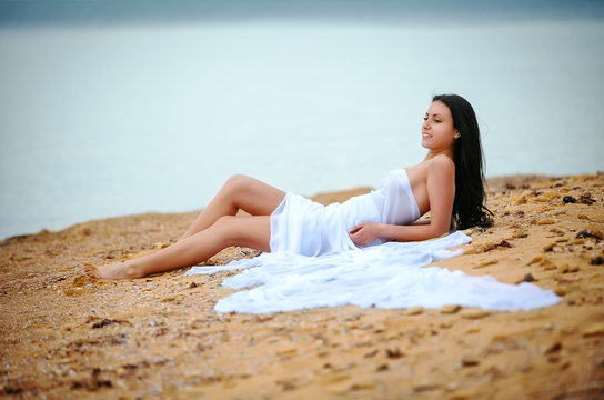 woman in white fabric on beach