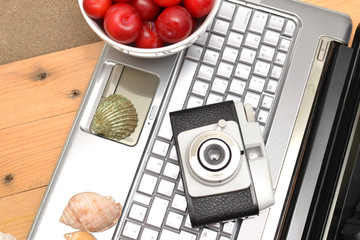 Laptop, shells, red plums and old camera
