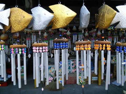 Collection of wind chimes made from metal and wood.