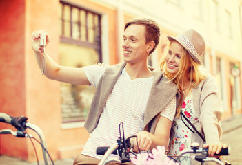 couple with bicycles taking photo with camera