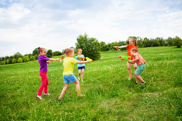 Children play with water guns on a meadow