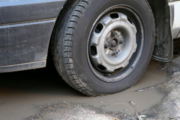 Bad road. Wheel and puddle.