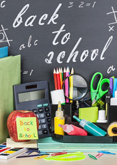school stationery laid on a background of chalkboard