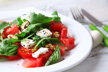 Salad with watermelon, feta, arugula and basil leaves
