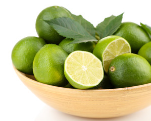 Fresh juicy limes in wooden bowl, isolated on white