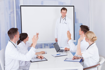Doctors Clapping For Colleague After Presentation In Hospital