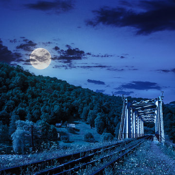 old railroad passes in mountain village at night