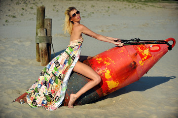 Beautiful fashion model in colorful dress posing at the beach.