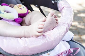 Feet of little girl in pram.