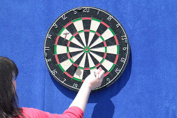 Woman removes darts from dartboard on blue wall at sunny day