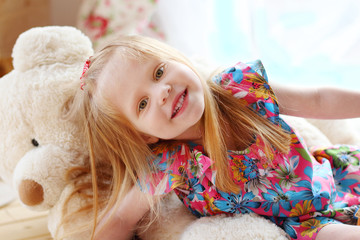 Pretty blonde little girl lies on big soft toy bear and smiles