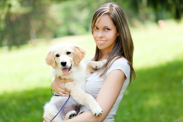 Beautiful girl with her dog at the park
