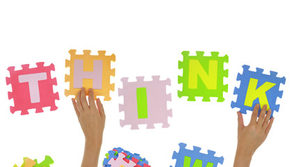 "Hands forming word ""Think"" with jigsaw puzzle pieces isolated"