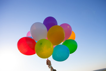 colorful balloons floats in a blue sky.