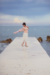 sea horizon on a white wooden bridge posing woman