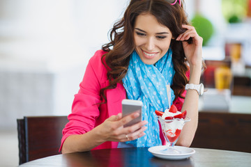 Young beautiful woman eating dessert and talking on the phone.