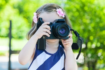 Little girl who takes pictures with a photo camera in park