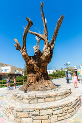 Tree with a carved face on the square in Matala, Greece Crete.