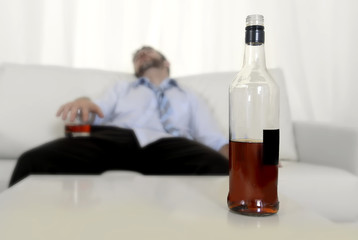drunk businessman wasted with whiskey sleeping in couch
