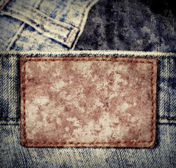 Grunge, scratched leather jeans label sewed on jeans.