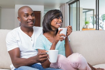 Happy couple relaxing on the couch having coffee