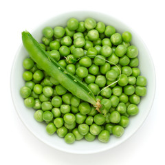 Fresh garden peas in a ceramic dish shot from above.With pod.