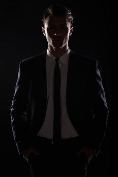 Handsome business man in black suite, backlight